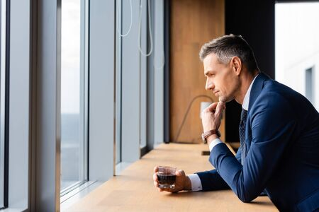 side view of pensive businessman in suit holding glass and looking through window