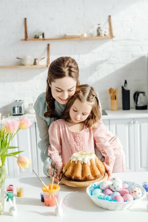attractive mother and happy child near easter eggs, decorative rabbits, easter bread and tulips