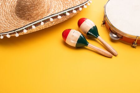 Wooden colorful maracas, tambourine and sombrero on yellow background 写真素材
