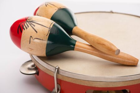 Selective focus of wooden maracas on tambourine on white background