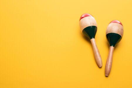 Top view of wooden maracas on yellow background 写真素材