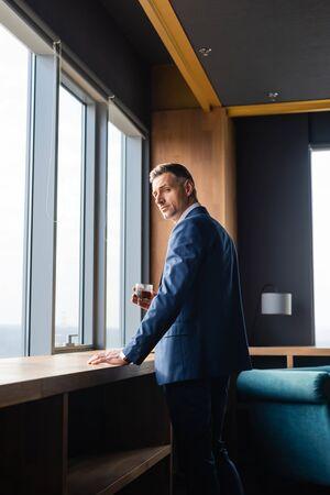 handsome businessman in suit holding glasses and looking away Reklamní fotografie