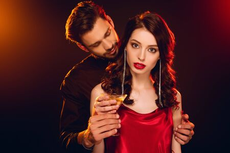Elegant woman in red dress holding glass of cocktail near handsome boyfriend on black background with lighting