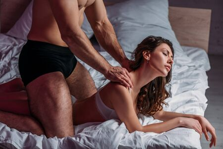 partial view of shirtless man making shoulders erotic massage to sexy girlfriend lying on bed with closed eyes