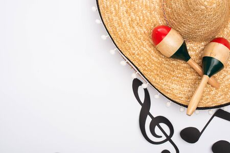 Top view of sombrero and maracas near paper cut music notes on white background 写真素材
