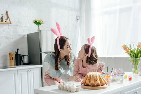 happy mother and daughter in bunny ears looking at each other near easter eggs