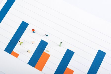Top view of people figures on surface of blue and red graphs isolated on white, equality concept