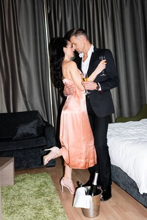 side view of boyfriend and girlfriend holding glasses and kissing in hotel