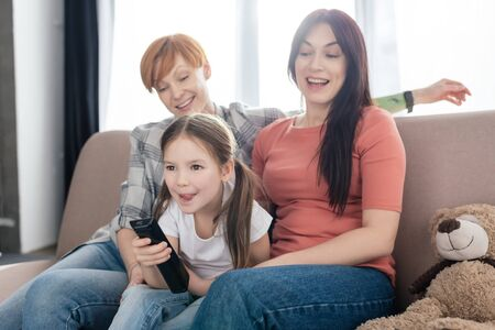 Cheerful kid with remote controller sitting near mothers on couch in living room