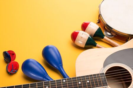 Wooden colorful and blue maracas with tambourine, castanets and acoustic guitar on yellow background