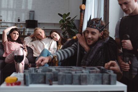 KYIV, UKRAINE - JANUARY 27, 2020: selective focus of men in fairy costumes playing labyrinth game while bored girls sitting on sofa
