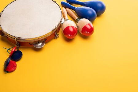 Wooden colorful and blue maracas with tambourine and castanets on yellow background