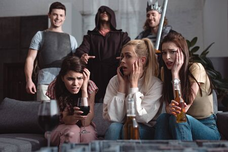 shocked girls drinking beer and wine while men in fairy characters costumes standing on background