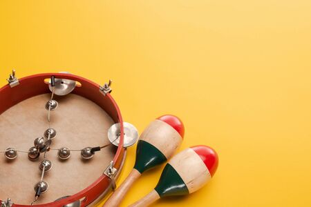 Tambourine near colorful wooden maracas on yellow background