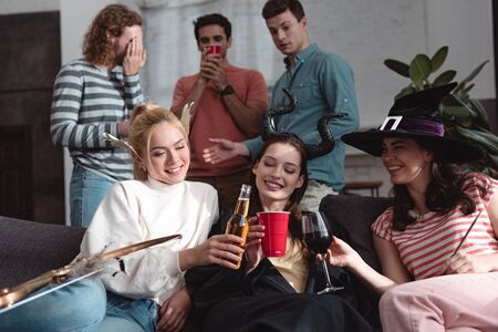 handsome men standing near cheerful girls drinking beer, wine and soda while sitting on sofa