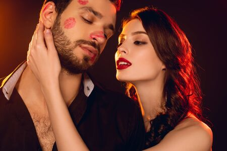 Attractive girl touching handsome boyfriend with lipstick prints on face on black background