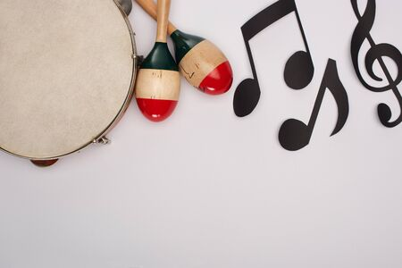 Top view of wooden maracas near tambourine and paper cut music notes on white background 写真素材