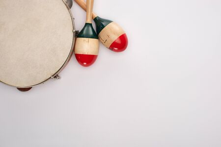 Top view of wooden maracas near tambourine on white background