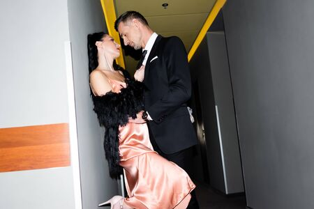 side view of boyfriend and girlfriend kissing and hugging in hotel