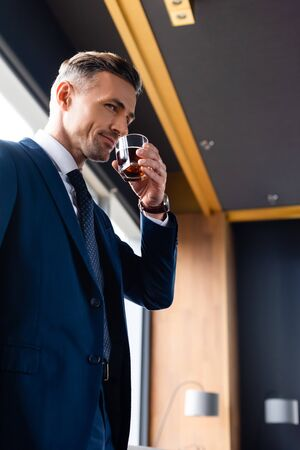 low angle view of smiling businessman in suit drinking cognac