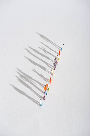 Top view of row of plastic people figures with shadow on white surface