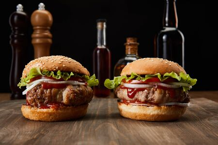 selective focus of two burgers on wooden surface near oil, vinegar and beer bottles, pepper and salt mills isolated on black
