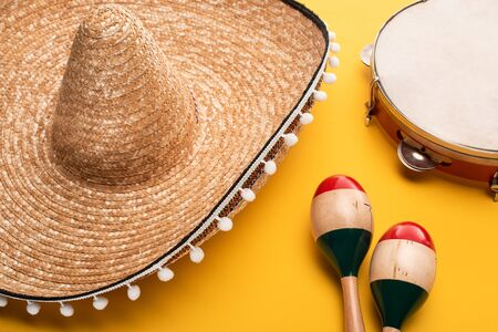 Wooden colorful maracas near sombrero and tambourine on yellow background