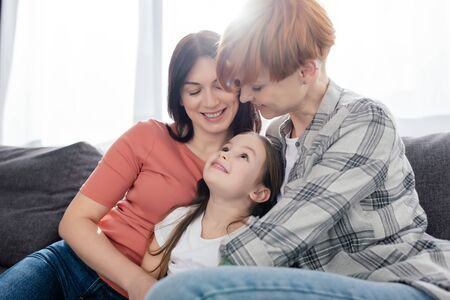 Same sex parents looking at smiling daughter on couch