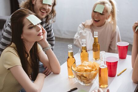 thoughtful girl playing name game with cheerful friends with sticky notes on foreheads Foto de archivo