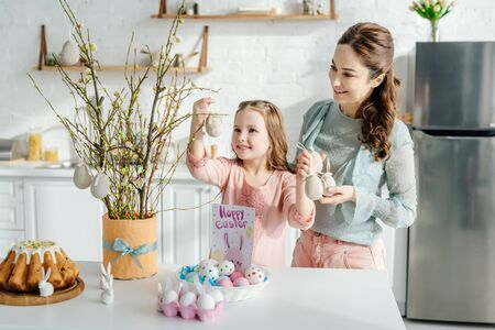 cheerful kid touching decorative easter egg near mother willow and decorative bunnies