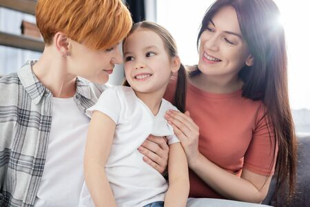 Same couple hugging smiling daughter on couch in living room