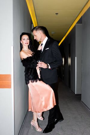 handsome boyfriend with glass hugging smiling girlfriend in hotel