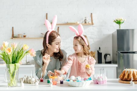 happy child and mother with bunny ears near chicken eggs, decorative rabbits, easter bread and tulips