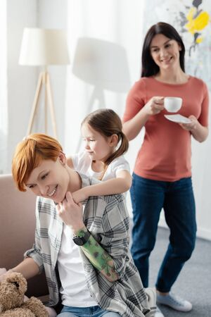 Selective focus of mother playing with daughter on couch near parent with coffee cup in living room