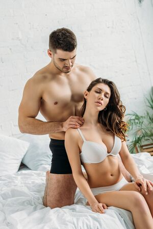 sexy young man making erotic shoulders massage to seductive girlfriend in lingerie Banque d'images