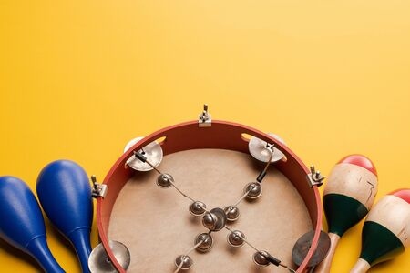 Close up view of tambourine near colorful and blue maracas on yellow background