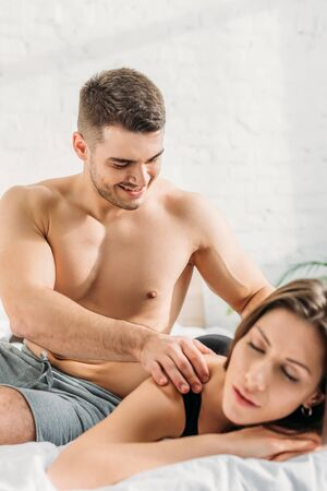 selective focus of sexy man making shoulders erotic massage to girlfriend lying and smiling with closed eyes Banque d'images