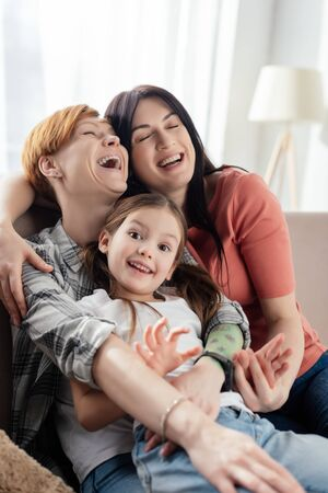 Selective focus of same parents laughing while embracing daughter on couch in living room Stock fotó