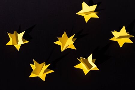 decorative yellow paper stars isolated on black