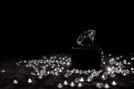 Diamond near gemstones on black velour isolated on black Stockfoto
