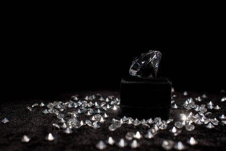 Diamond near gemstones on black velour isolated on black Stock Photo