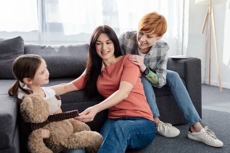 Smiling same sex family sitting near daughter with teddy bear in living room