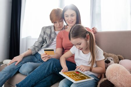 Child using digital tablet with e-health app near smiling same sex parents with credit card on couch
