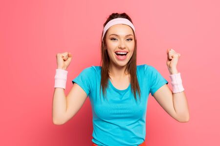 cheerful sportswoman showing winner gesture while smiling at camera on pink background