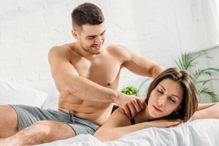 handsome shirtless man making shoulders erotic massage to attractive girlfriend lying with closed eyes Banque d'images