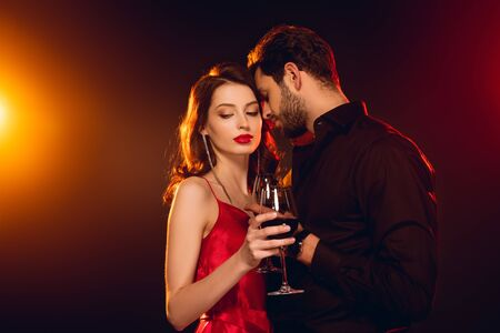 Handsome man holding glass of red wine near elegant girlfriend on black background with lighting Imagens