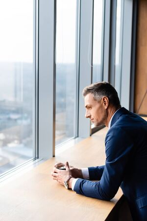 side view of businessman in suit holding glass and looking through window