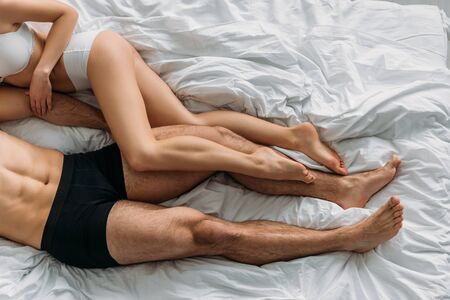 top view of sexy young couple in underwear lying on white bedding, cropped view