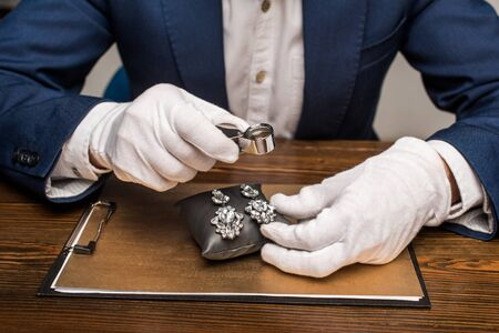Cropped view of jewelry appraiser holding magnifying glass and earnings on board on table isolated on grey