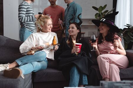 cropped view of men standing near cheerful girls in fairy costumes drinking beverages on sofa